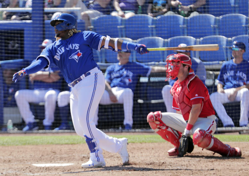 FILE - In this Feb. 28, 2019 file photo, Toronto Blue Jays' Vladimir Guerrero Jr., left, follows through with a double as Philadelphia Phillies catcher Andrew Knapp looks on in the third inning of a spring training baseball game in Dunedin, Fla. Just two years removed from a second consecutive ALCS appearance, the Blue Jays have turned over the core of those postseason teams and started transitioning to the future. All over the diamond this season, young players will be given the opportunity to establish themselves. (AP Photo/Lynne Sladky)