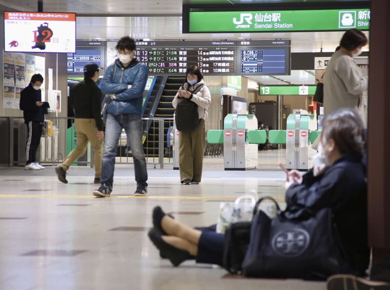 People sit on the floor at a station as train services are suspended following an earthquake in Sendai