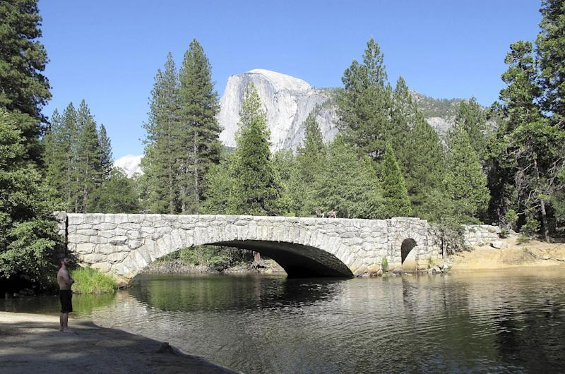 This June 12, 2012 photo shows Yosemite National Park's Stoneman Bridge, a single, arching span faced with rough-hewn granite, provides a dramatic foreground to Half Dome, the park's most iconic feature. Under proposed plans for restoring the natural flow of the Merced River, it is being considered for removal. This month the National Trust for Historic Preservation placed the 80-year-old Stoneman and two similar bridges in Yosemite Valley on its most endangered list, saying these early examples of natural park architecture should be protected. (AP Photo/Tracie Cone)
