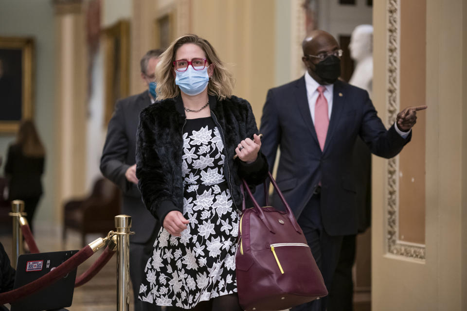 FILE - In this Feb. 9, 2021, file photo Sen. Kyrsten Sinema, D-Ariz., and Sen. Raphael Warnock, D-Ga., right, arrive at the Capitol in Washington. President Joe Biden called out two fellow Democrats on Tuesday in explaining why he hasn't enacted some of the most ambitious elements of his agenda, noting that slim majorities in the House and evenly divided Senate have hamstrung legislative negotiations around key issues like voting rights. It appeared to be a veiled reference to Democratic Sens. Joe Manchin and Sinema, both of whom have frustrated Democrats with their defense of the filibuster (AP Photo/J. Scott Applewhite, File)