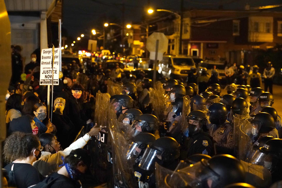 Protesters confront police during a march, Tuesday Oct. 27, 2020, in Philadelphia. Hundreds of demonstrators marched in West Philadelphia over the death of Walter Wallace, a Black man who was killed by police in Philadelphia on Monday. Police shot and killed the 27-year-old on a Philadelphia street after yelling at him to drop his knife. (AP Photo/Matt Slocum)