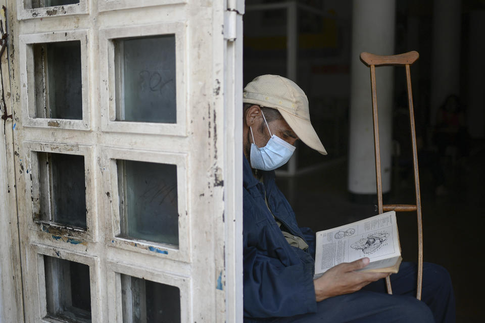 An elderly man who uses a crutch due to having lost half his leg reads a book at a cultural center in La Pastora neighborhood of Caracas, Venezuela, Monday, June 29, 2020, amid the COVID-19 pandemic. (AP Photo/Matias Delacroix)