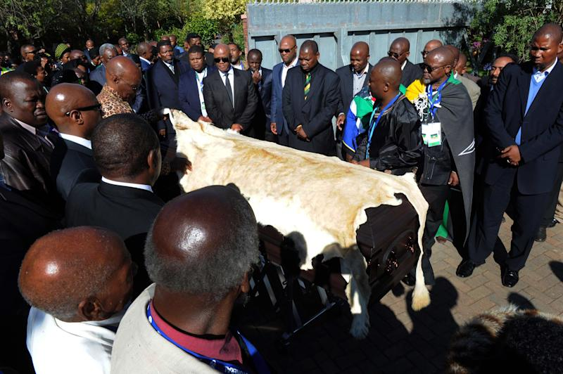 Nelson Mandela's grandson Mandla Mandela, right, watches as local chiefs drape the casket of former South African President Nelson Mandela with a lion skin as it arrives at the Mandela residence in Qunu, South Africa, December 14, 2013. Mandela will be put to rest after funeral services on Sunday. (AP Photo/Elmond Jiyane, GCIS)