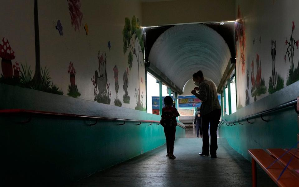 A teacher and student walk together on the first day back to in-person classes during the Covid-19 pandemic at a public school in Brasilia, Brazil - Eraldo Peres/AP