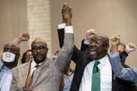 Philonise Floyd, brother of George Floyd, left, and attorney Ben Crump raise their hands in triumph during a news conference after the murder conviction against former Minneapolis police Officer Derek Chauvin in the killing of George Floyd, Tuesday, April 20, 2021, in Minneapolis. (AP Photo/John Minchillo)