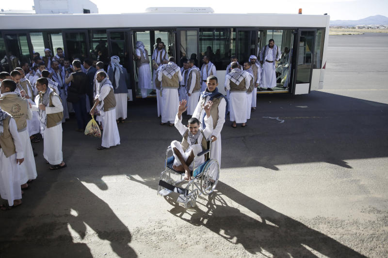 A Yemeni prisoner, center, gestures during his arrival with his fellows after being released by the Saudi-led coalition in the airport of Sanaa, Yemen, Thursday, Nov. 28, 2019. The International Committee of the Red Cross says over a hundred rebel prisoners released by the Saudi-led coalition have returned to Houthi-controlled territory in Yemen, a step toward a long-anticipated prisoner swap between the warring parties. (AP Photo/Hani Mohammed)