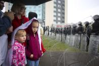 People with their childs stand at a barbed wire fence in front of a police line toward the Independence Palace, residence of the President Alexander Lukashenko, during Belarusian opposition supporters rally in Minsk, Belarus, Sunday, Sept. 6, 2020. Sunday's demonstration marked the beginning of the fifth week of daily protests calling for Belarusian President Alexander Lukashenko's resignation in the wake of allegedly manipulated elections. (AP Photo/TUT.by)