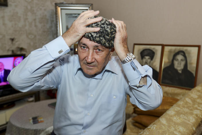 """Velyeddin Ismayilov, 77, an Azerbaijani refugee from Kalbajar region puts on a national hat prior to his interview with the Associated Press in Baku, Azerbaijan, Wednesday, Nov. 25, 2020. Ismayilov says he fled Kalbajar with his wife and three young children, and his big house is now ruined. But he is prepared to return and restore his home town, and build a new house for his family. """"With my grown-up children, grandchildren we will build an even better house,"""" he said. (AP Photo/Aziz Karimov)"""