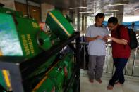 Men use their phones as alms boxes with QR codes are collected on a cart after Friday prayers at Istiqlal mosque in Jakarta