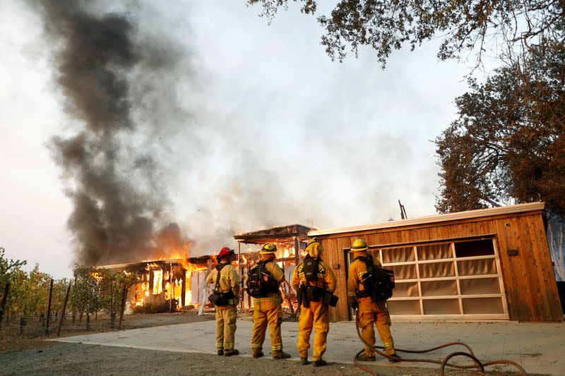 FILE PHOTO: A group of firefighters look on as a house burns during the wind-driven Kincade Fire in Healdsburg, California