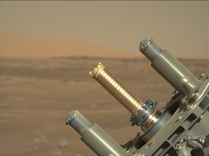 perseverance rover robotic arm holds up golden tube for coring samples against mars plains background