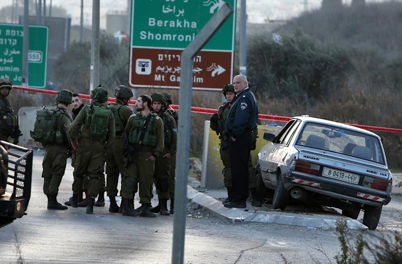 Israeli security forces gather at the site of a car ramming attack at the Huwara checkpoint near the West Bank city of Nablus, on December 26, 2015 (AFP Photo/Jaafar Ashtiyeh)