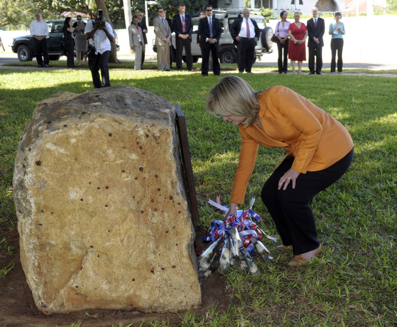 U.S. Secretary of State Hillary Rodham Clinton lays flowers in front of the memorial to the 1998 Bombing of the U.S. Embassy in Dar es Salaam, Tanzania, on the property of the new U.S. Embassy in Dar es Salaam, Sunday, June 12, 2011.  (AP Photo/Susan Walsh, Pool)