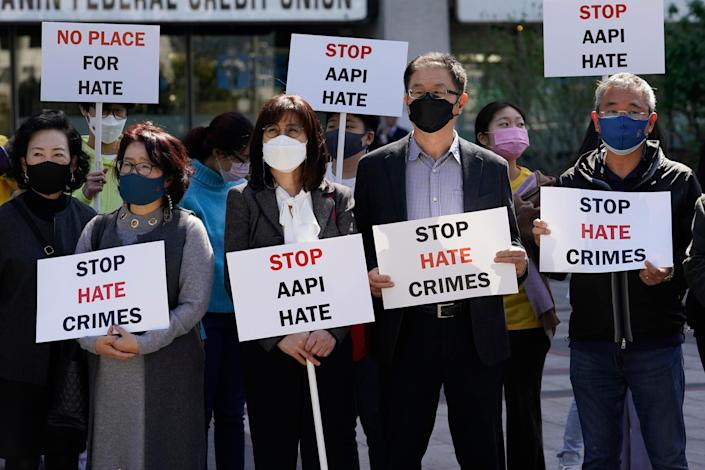 Demonstrators holds signs during a press conference in Los Angeles calling to a halt on violence against Asian Americans.