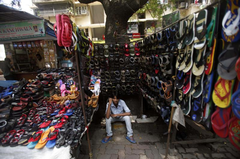 An Indian roadside shoe vendor waits for customers at a market in Mumbai, India, Monday, Sept. 17, 2012. India's central bank, Reserve Bank of India, on Monday cut the cash reserve ratio as it tries to kick-start flagging growth and welcomed government efforts to open Asia's third-largest economy to more foreign investment. The government's announcement allowing foreign companies in retail and raising the price of diesel has met with protests from opposition parties and some of the ruling Congress party's coalition partners. (AP Photo/Rafiq Maqbool)