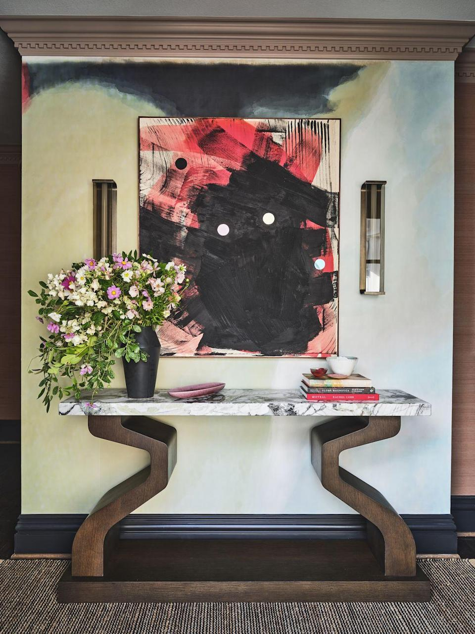 """<p>The extended back hallway is a threshold everyone coming in from the garage has to pass through, so Walsh really wanted to evoke a feeling of being welcomed home with a sumptuous runner from <a href=""""https://www.newmoonrugs.com/"""" rel=""""nofollow noopener"""" target=""""_blank"""" data-ylk=""""slk:New Moon Rugs"""" class=""""link rapid-noclick-resp"""">New Moon Rugs</a> and a place to make an important mental transition from work or school life to life at home. Since there was so much wall space to play with, she turned this area into a gallery. Her lone piece of furniture is a stunning sculptural console from FBC London and the walls are filled with artworks from Conduit in Dallas among others that help the brain dissociate from the stress of the day. Walsh hopes this space helps one become present in his or her home before connecting with the rest of the family.</p>"""