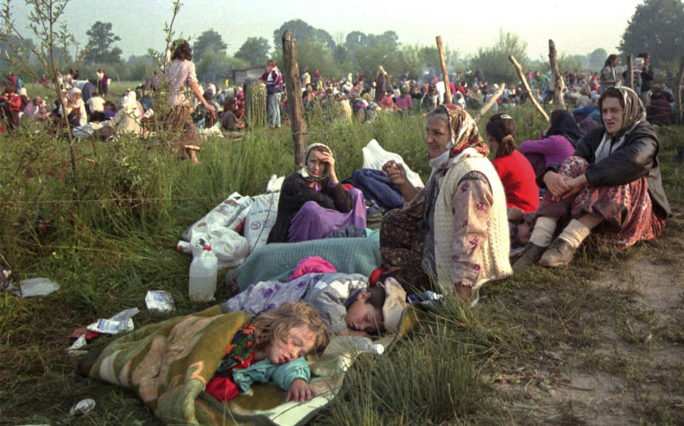 FILE - In this July 14, 1995, file photo, refugees from Srebrenica who had spent the night in the open air, gather outside the U.N. base at Tuzla airport. Twenty-six years after the July 1995 Srebrenica massacre, the only episode of Bosnia's 1992-95 war to be legally defined as genocide, its survivors continue to grapple with the horrors they endured while also confronting increasingly aggressive downplaying and even denial of their ordeal. (AP Photo/Darko Bandic, File)