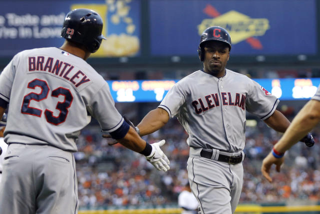 Cleveland Indians' Michael Bourn is congratulated by Michael Brantley (23) after scoring against the Detroit Tigers on a single by Carlos Santana in the first inning of a baseball game Saturday, Aug. 31, 2013, in Detroit. (AP Photo/Duane Burleson)