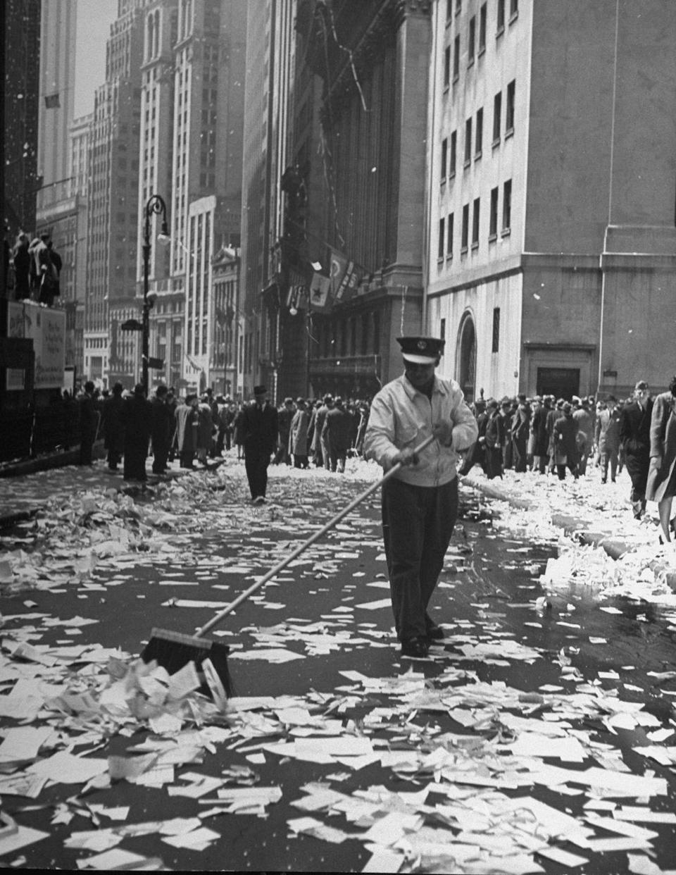 <p>A sanitation worker sweeps up a confetti-covered Times Square.</p>