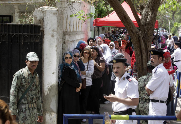 Egyptian soldiers and policemen stand guarding as women line up outside a polling station in Cairo, Egypt, Thursday, May 24, 2012. In a wide-open race that will define the nation's future political course, Egyptians voted Thursday on the second day of a landmark presidential election that will produce a successor to longtime authoritarian ruler Hosni Mubarak. (AP Photo/Amr Nabil)