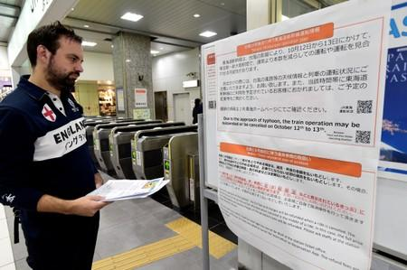An England rugby supporter reads a travel warning sign at Hamamatsu railway station, regarding Typhoon Hagibis and possible train suspensions and cancellations in Hamamatsu