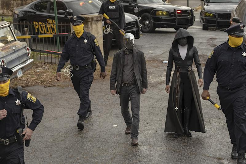 "Eccentric masked man Looking Glass (Tim Blake Nelson, center) is a part of a Tulsa police force who hide their identities in ""Watchmen."""