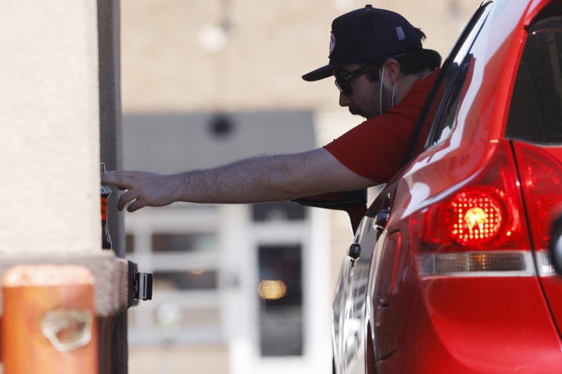 A motorist reaches to the jar to leave a tip for workers at a drive-thru window of a Dunkin Donuts as a stay-at-home order reamins in force for residents while still dealing with the dangers of the new coronavirus Tuesday, April 28, 2020, in Denver. (AP Photo/David Zalubowski)