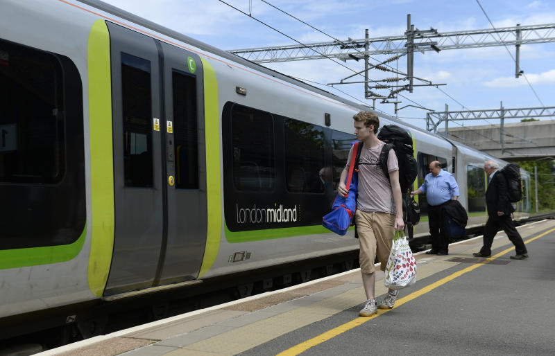 Commuters wait to board a London Midland train at Tile Hill train station in Coventry