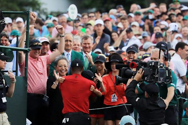 Tiger Woods celebrates his Masters victory Sunday with son Charlie Axel, his mother Kultida and daughter Sam Alexis as he leaves the 18th green at Augusta National (AFP Photo/DAVID CANNON)