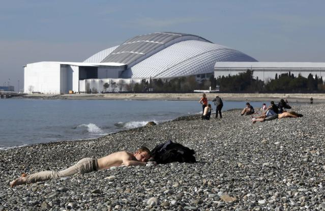 Local residents and visitors enjoy sun-bathing along the Black Sea near the Olympic Park during the 2014 Sochi Winter Olympics, February 12, 2014 . REUTERS/Reinhard Krause (RUSSIA - Tags: SPORT OLYMPICS ENVIRONMENT)