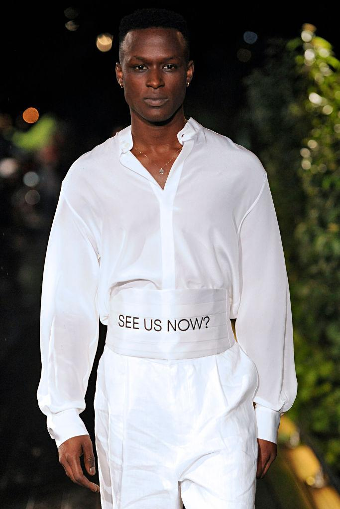 """<p>In another look, a male model walks down the Pyer Moss runway wearing an all-white ensemble with a white cummerbund asking the question, """"See us now?"""" (Photo: Getty) </p>"""