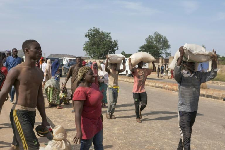 People in Nigerian city Jos carried off bags of food on their heads during a mass looting of a warehouse