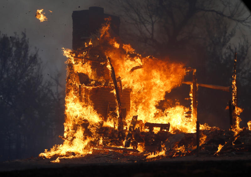 A home burns during a large wildfire Friday, Aug. 3, 2012 in Luther, Okla. A wildfire whipped by gusty, southerly winds swept through rural woodlands north and south of Oklahoma City on Friday, burning several homes as firefighters struggled to contain it in 113-degree heat.  (AP Photo/The Oklahoman, Bryan Terry)