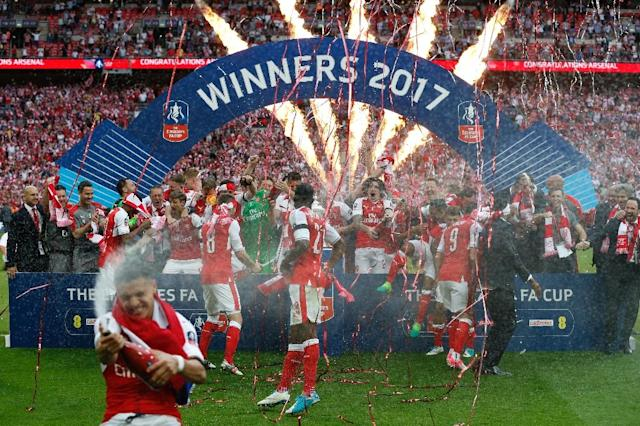 Arsenal's Alexis Sanchez sprays champagne as the team celebrates their win over Chelsea on the pitch after their English FA Cup final at Wembley stadium in London on May 27, 2017 (AFP Photo/Ian KINGTON)