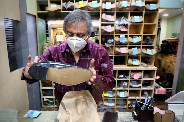 Eddie's Shoes owner Hugo Adraix reviews the stitching of a re-soled shoe in his shop in Rockefeller Center on Dec. 22, 2020. (Elise Wrabetz / NBC News)