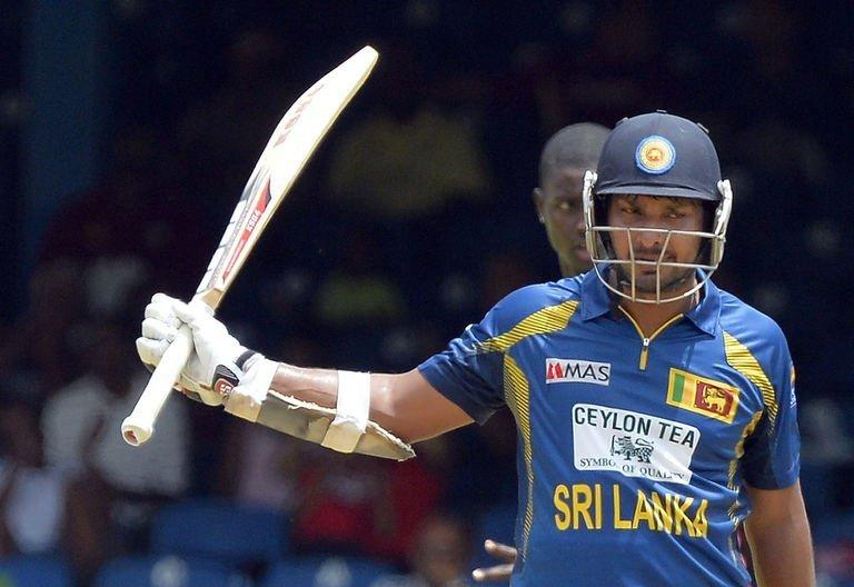 Sri Lanka's Kumar Sangakkara raises his bat after scoring his half century during the fifth match of the Tri-Nation series between Sri Lanka and West Indies at the Queen's Park Oval stadium on July 8, 2013. Sri Lanka weathered a middle-order revival by the West Indies and held on for a 39-run victory on the Duckworth/Lewis Scoring Method in a rain-affected fifth match of the Tri-Nation Series