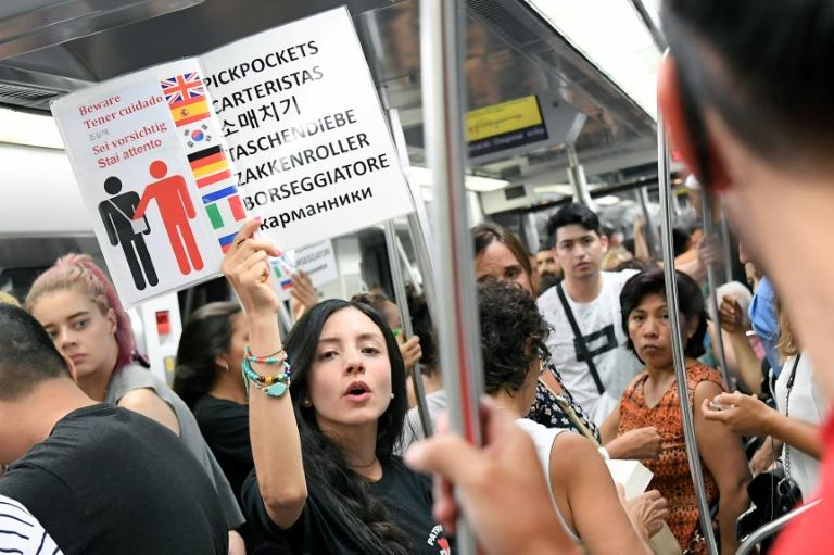 A citizen on patrol holds up a multi-language sign to warn metro passengers of pickpockets in Barcelona