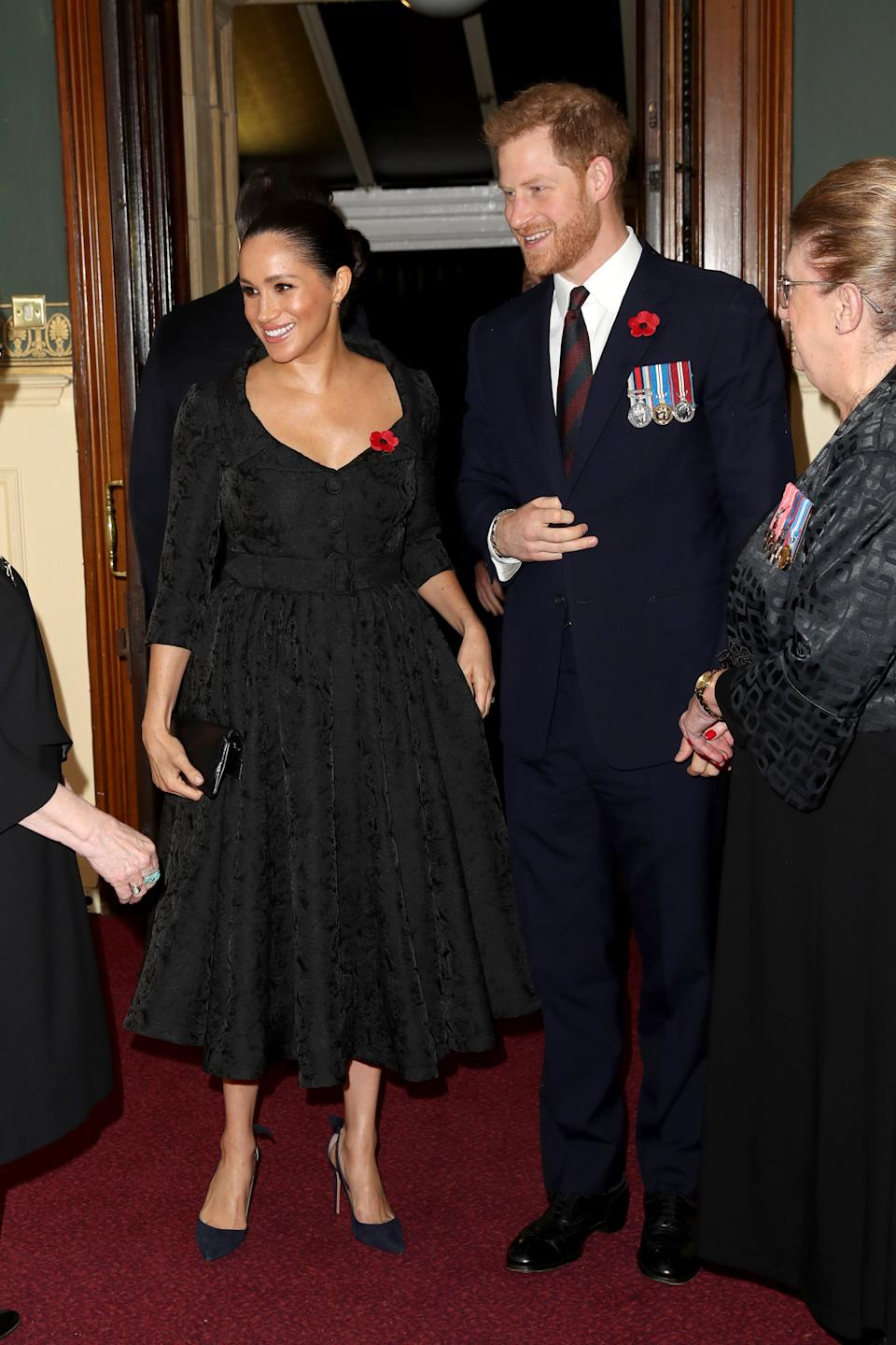 Meghan Markle stunned a brocade black dress by Erdem as she arrived with Prince Harry at the Royal Albert Hall in London [Image: Getty]