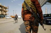 An Iraqi policeman carries a weapon at a checkpoint in Falluja