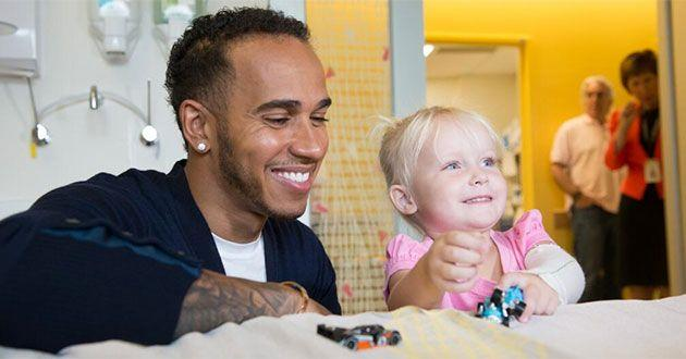 British racing star Lewis Hamilton meets some of his smallest fans, Sharnie McDonald, at the Royal Children's Hospital. Photo: RCH