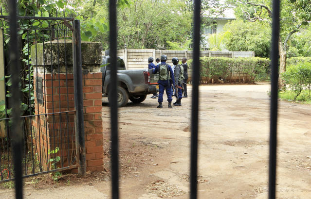 Armed police officers stand outside the residence of Evan Mawarire, an activist and pastor who helped mobilize people to protest against the hike in fuel prices, following his arrest in Harare, Zimbabwe, Wednesday, Jan. 16, 2019. Mawarire was arrested Wednesday for allegedly inciting violence in the protests against the government's increase in fuel prices. (AP Photo/Tsvangirayi Mukwazhi)
