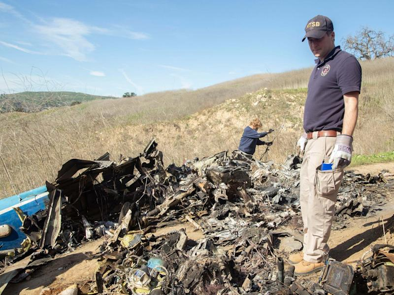 NTSB investigators search through the wreckage of the helicopter that crashed carrying Kobe Bryant and his daughter: AP