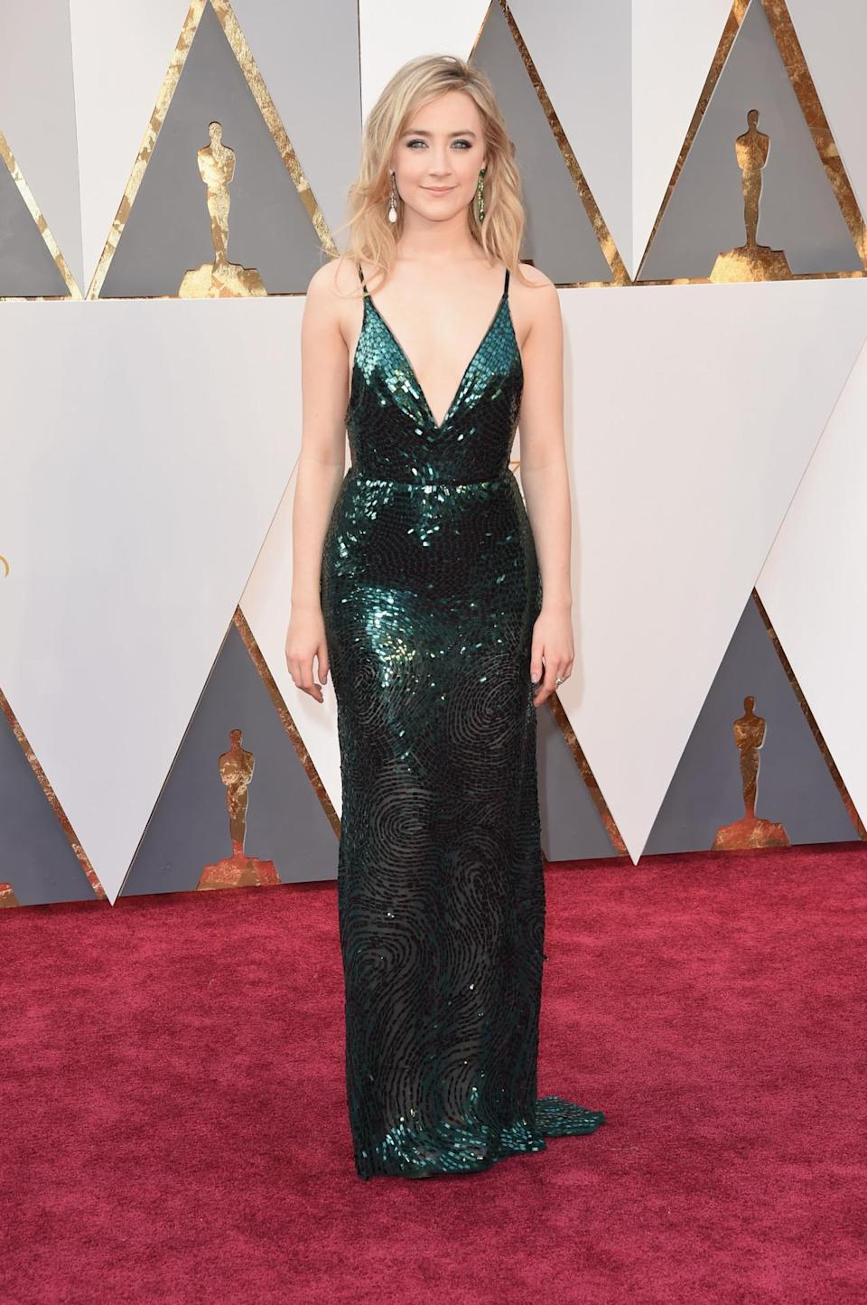 <p>Saoirse Ronan wore an emerald green Calvin Klein Collection gown to honor her home country of Ireland. To take the sequin look to the next level, she also accessorized with mismatched earrings from Chopard: One is made of 18-carat emeralds and the other of 5.7-carat jadeite.<i> <i>(Photo: Getty Images)</i></i></p>