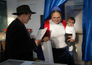 Baby Sonia is held by her mother as she casts her vote at a polling station in Sintesti, Romania, Sunday, Nov. 10, 2019. Romania held a presidential election Sunday after a lackluster campaign that has been overshadowed by the country's political crisis, which saw a minority government installed just a few days ago. (AP Photo/Vadim Ghirda)