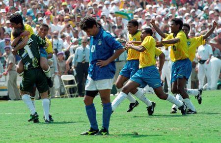 FILE PHOTO: Brazilian striker Bebeto leaps into the arms of goalkeeper Claudio Taffarel (L) as Italy's Roberto Baggio (C) stares at the ground after missing the penalty kick which cost his team the World Cup during the final in Pasadena, California July 17, 1994. REUTERS/Andre Camara/File Photo