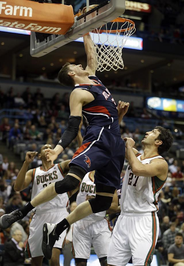 Atlanta Hawks' Mike Muscala goes up to shoot past Milwaukee Bucks' Zaza Pachulia (27) during the first half of an NBA basketball game on Wednesday, April 16, 2014, in Milwaukee. (AP Photo/Morry Gash)
