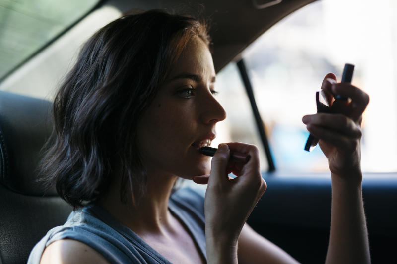 Portrait of young woman applying make up inside of a cab