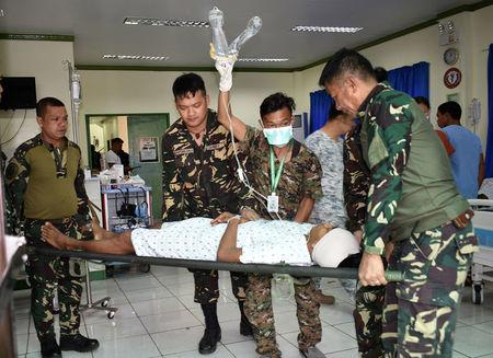 A soldier lays on a stretcher and is carried by his comrades after sustaining wounds in a gunfight with Islamic State-linked Abu Sayyaf militants in Talipao town