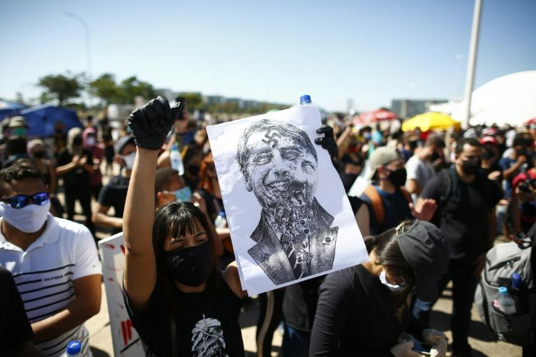 Many protesters against President Jair Bolsonaro in Brasilia were dressed in black and wore face masks (AFP Photo/Sergio LIMA)