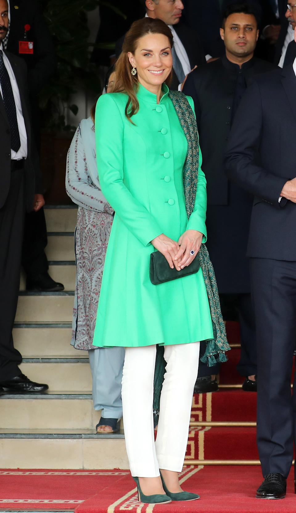 For her second engagement, the Duchess wore a new green Catherine Walker coat with white trousers by Maheen Khan. A suede green clutch bag and matching heels completed the look, along with a scarf by Satragni and earrings by Zeen. <em>[Photo: Chris Jackson/Getty Images]</em>